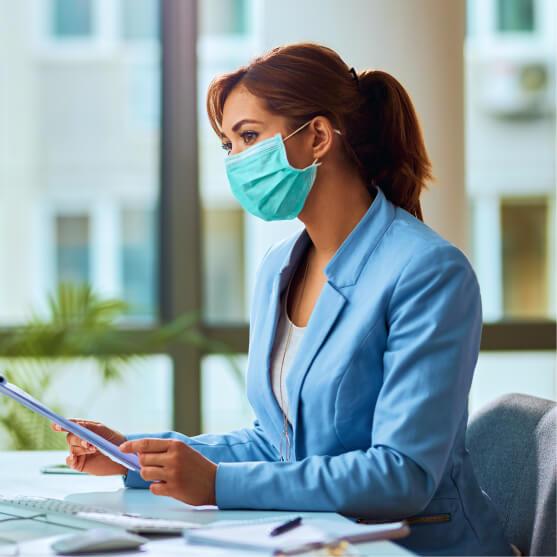 Mulher trabalhando em escritório utilizando máscara